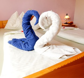 Zwei Schwäne aus Handtücher auf dem Bett im Winzerzimmer.