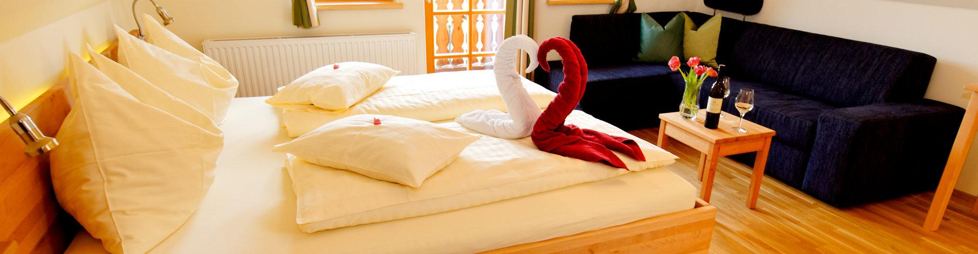 Winzerzimmer mit Schwänen aus Handtüchern auf dem Bett und einem ausziehbarem Sofa sowie ein Balkon und Klimaanlage, gratis W-Lan und vieles mehr...